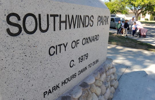 A family crosses the street after playing at Southwinds Park in Oxnard.