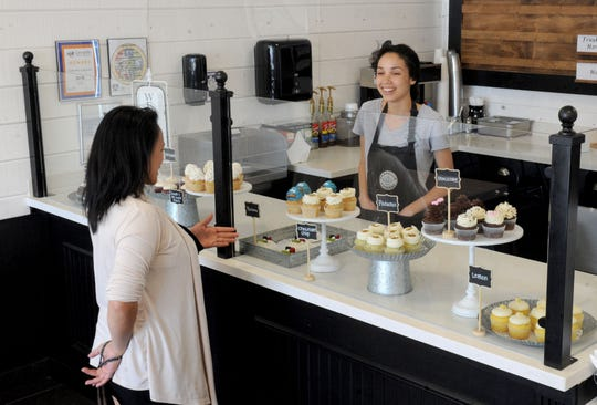 Roxanne Amos, left, chats with Camryn Weisenberger, a customer service representative at Camarillo Cupcake, before deciding which cupcake to order.  The bakery opened in May in the Carmen Plaza.