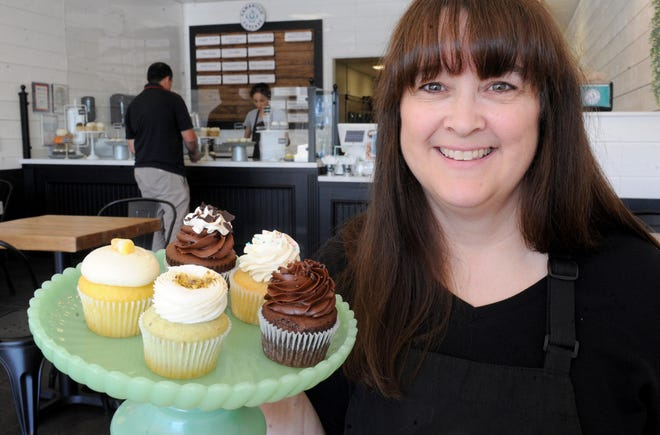 Gina Stymacher, owner of Camarillo Cupcake, poses with different flavors of cupcakes at the shop, which opened in May in the Carmen Plaza. In addition to core flavors like lemon and red velvet, Camarillo Cupcake introduces a new batch of limited-time-only flavors every Thursday. Gluten-free and vegan options are available.