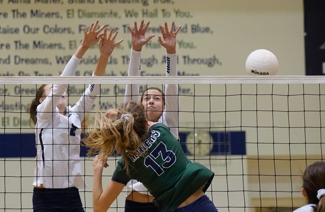 El Diamante's Preslee Nunez gets a ball through the block of two Redwood defenders during a West Yosemite League high school volleyball match between Redwood and El Diamante at El Diamante in Visalia.