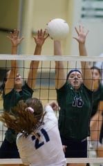 El Diamante's Gillian Nutter and Alyssa Stevens block the hit of Redwood's Brooklyn Bailey during a West Yosemite League high school volleyball match between Redwood and El Diamante