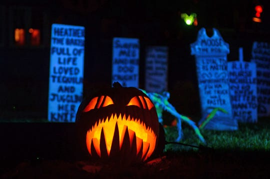 A carved and lighted pumpkin placed among what appears to be tombstones is a stunning Halloween sight.