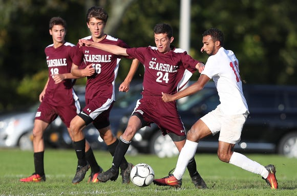 Scarsdale's Benjamin Rubin (24) and North Rockland's Kenji Harper (10) battle for ball control during boys soccer action at Quaker Ridge School in Scarsdale Oct. 16, 2018. Scarsdale won the game 3-0.