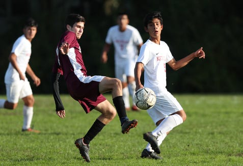 Scarsdale's Adrian Lim (22) moves the ball away from North Rockland's Brayan Paredes (5) during boys soccer action at Quaker Ridge School in Scarsdale Oct. 16, 2018. Scarsdale won the game 3-0.