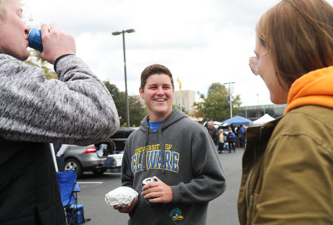 University of Delaware student Mike Rutecki of Springifield Pa. (center) hangs out in the tailgate with cousin Dan Rutecki of Broomall, Pa., and Kayla Feairheller of West Chester, Pa. before Delaware took on Elon at Delaware Stadium Saturday.