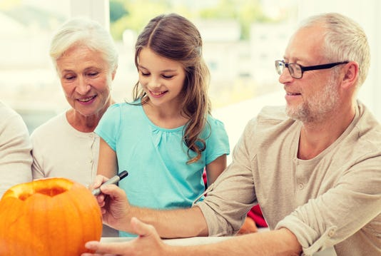 Happy Family Sitting With Pumpkins At Home