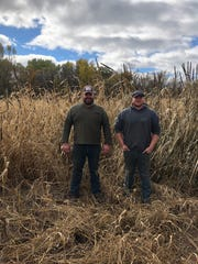 Jeff Lake and his son, Jake (right) stand near a buffer they planted with sorghum, clover, buckwheat and millet to improve soil health as well as provide cover for wildlife on their Dunn County farm.
