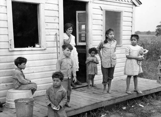 In the town of Plymouth in 1948, a Mexican woman and her six children stand on the porch of the multiple-family housing provided to them by the pea cannery for which their husband and father works.