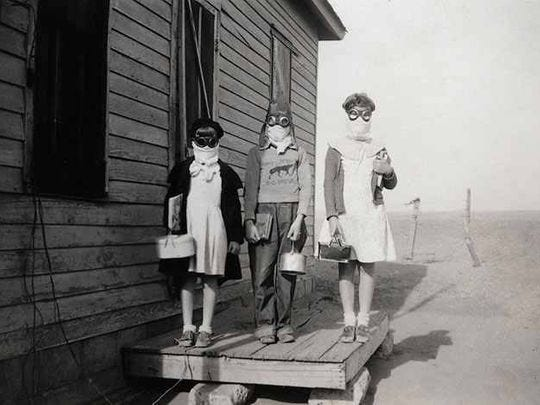 Children attired in goggles and homemade masks in order to avoid the dust of the 1930s.