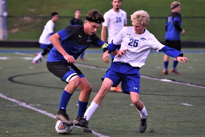 Zanesville's Jack Thorne makes a move against a Cambridge defender in Tuesday's 6-1 victory in Division II sectional tournament action.