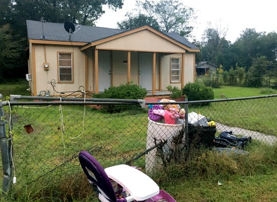 Toys, a discarded high chair and police evidence tape are part of the trash outside a home on Tuesday, Oct. 16, 2018, where a 20-month-old girl was found dead inside an oven on Monday evening at the residence, in Shaw, Miss.