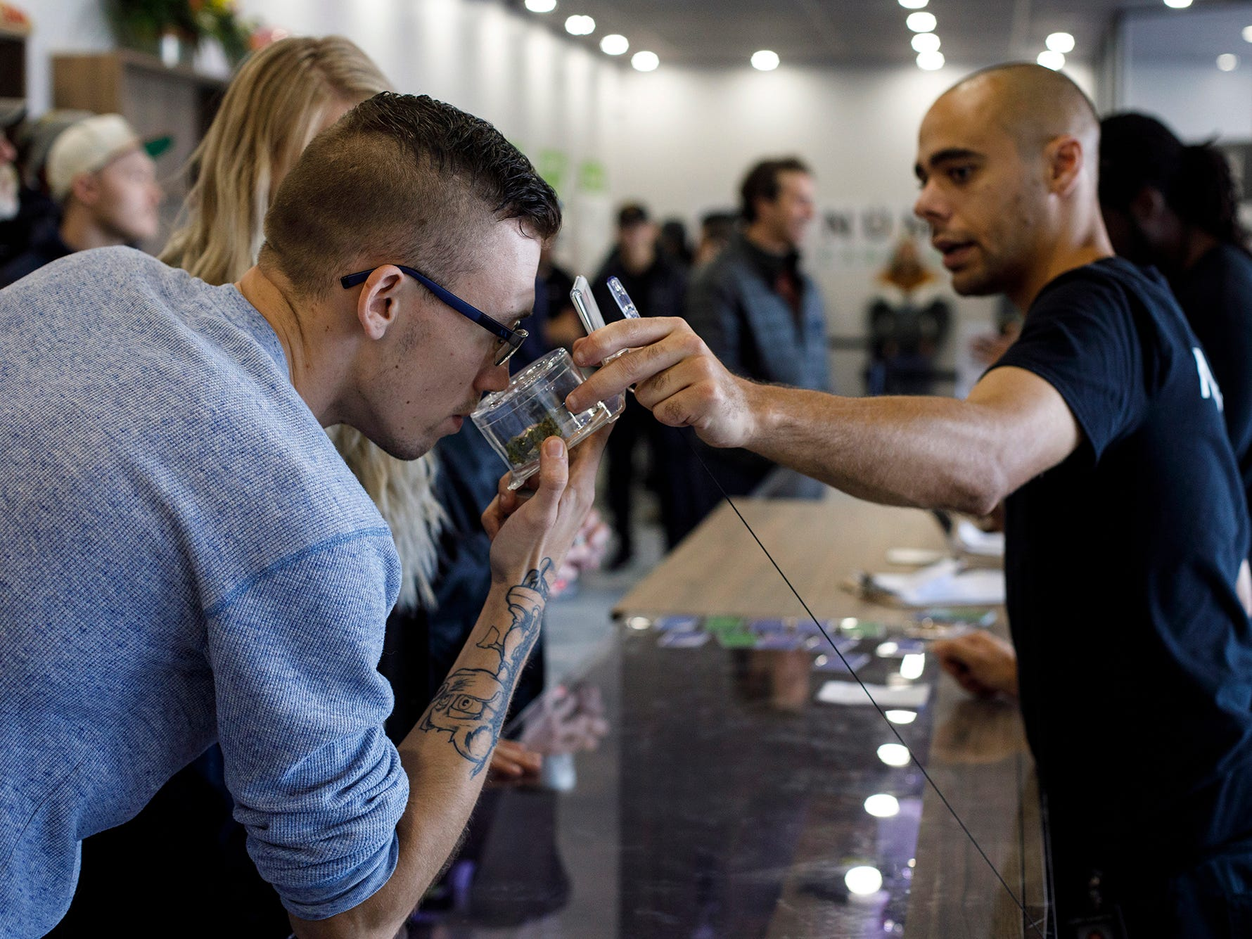 Kyle Bell, of Numo Cannabis, helps a customer decide on his purchase of legal marijuana in Edmonton, Alberta, Wednesday, Oct. 17, 2018.