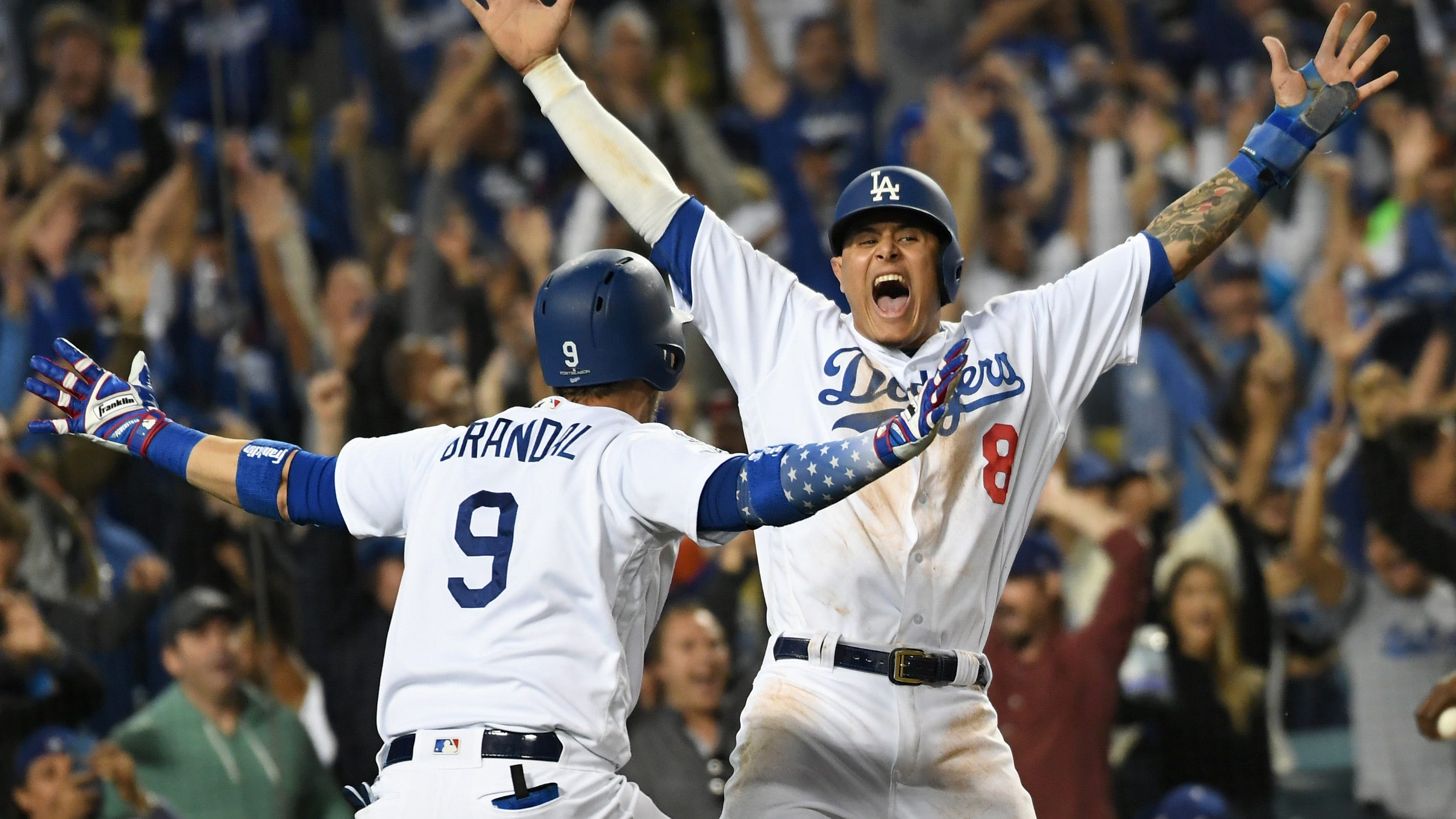 Dodgers shortstop Manny Machado celebrates with catcher Yasmani Grandal after scoring on an RBI single in the 13th inning.