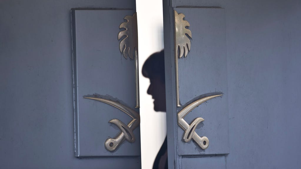 A consulate staff member is seen behind the entrance of Saudi Arabia's diplomatic compound in Istanbul, on Oct. 17, 2018.