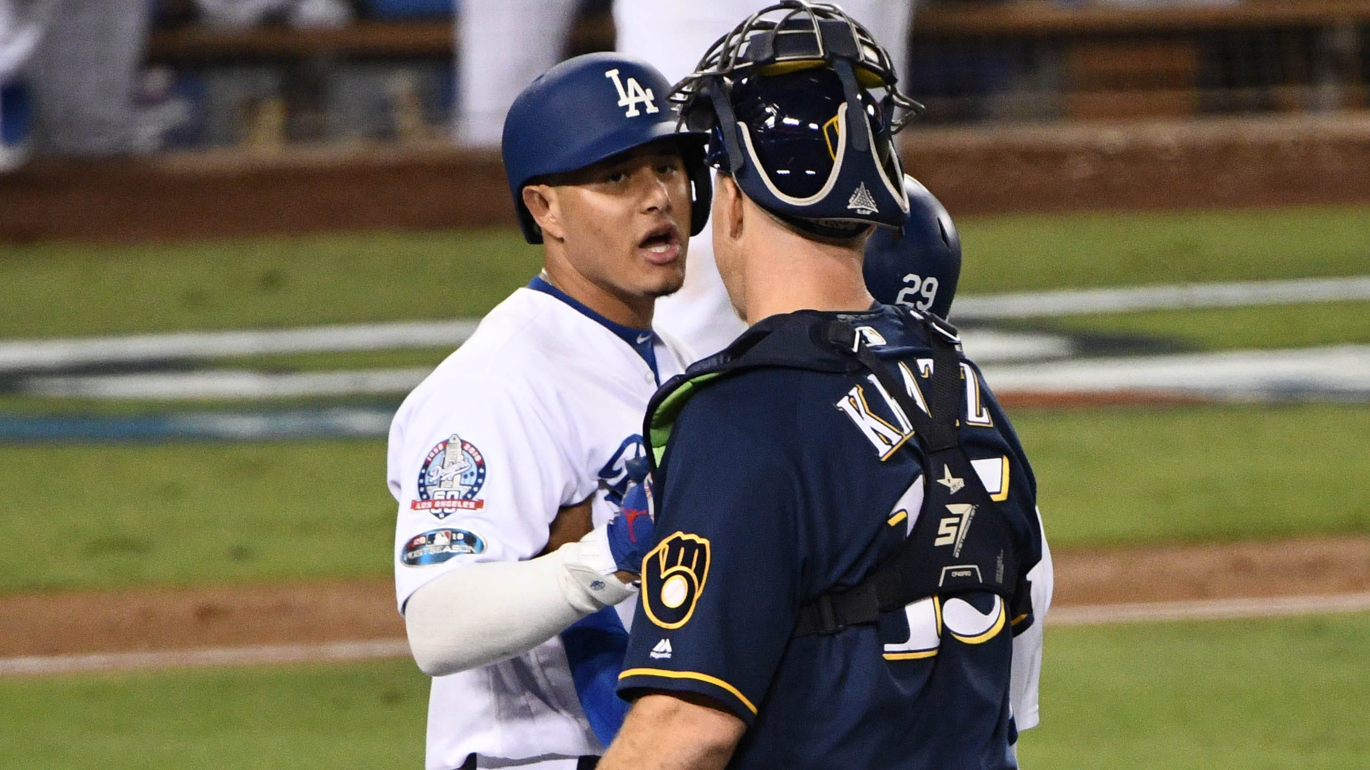 Dodgers shortstop Manny Machado and Brewers catcher Erik Kratz react after Machado clipped first baseman Jesus Aguilar on the way to first base.