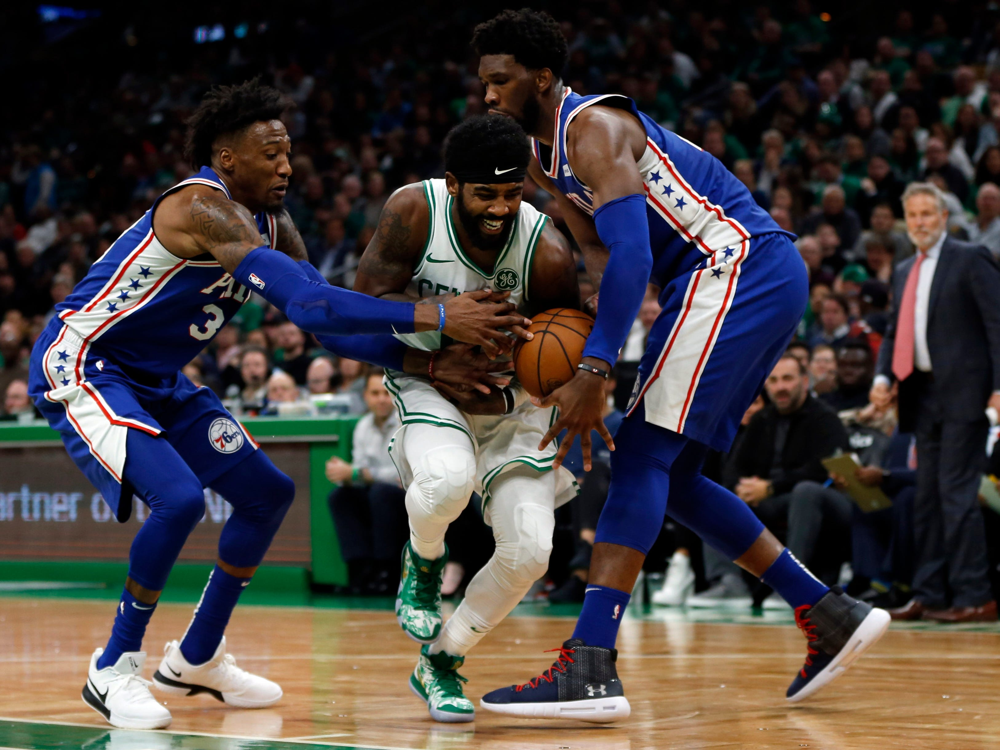 Oct. 16: Boston Celtics guard Kyrie Irving drives between Philadelphia 76ers center Joel Embiid and forward Robert Covington during the second half at TD Garden.