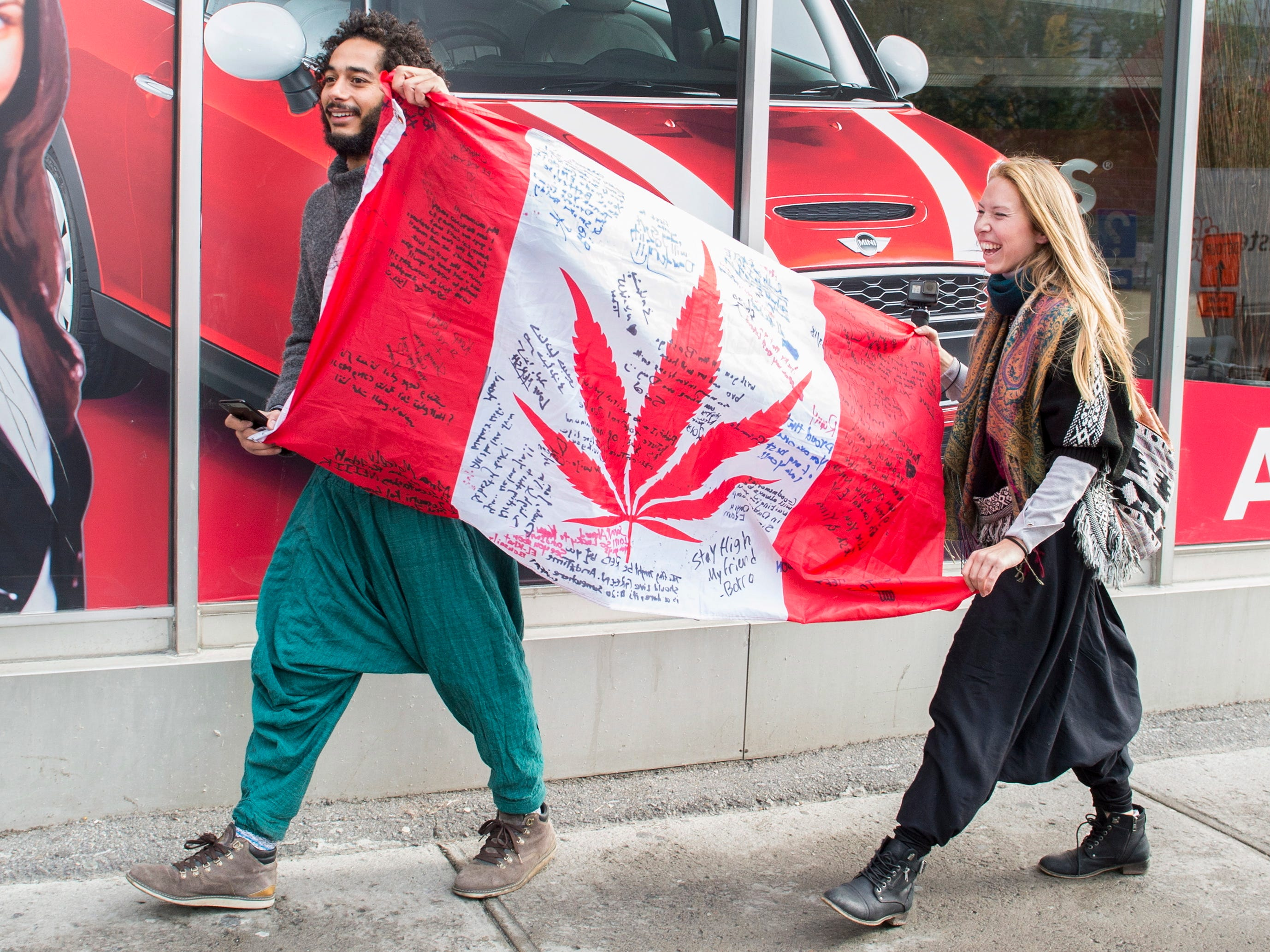 People hold up a Canadian flag with a marijuana logo on it outside a government cannabis store in Montreal, Wednesday, Oct. 17, 2018. Canada became the largest country with a legal national marijuana marketplace as sales began early Wednesday. (Graham Hughes/The Canadian Press via AP) ORG XMIT: GMH122