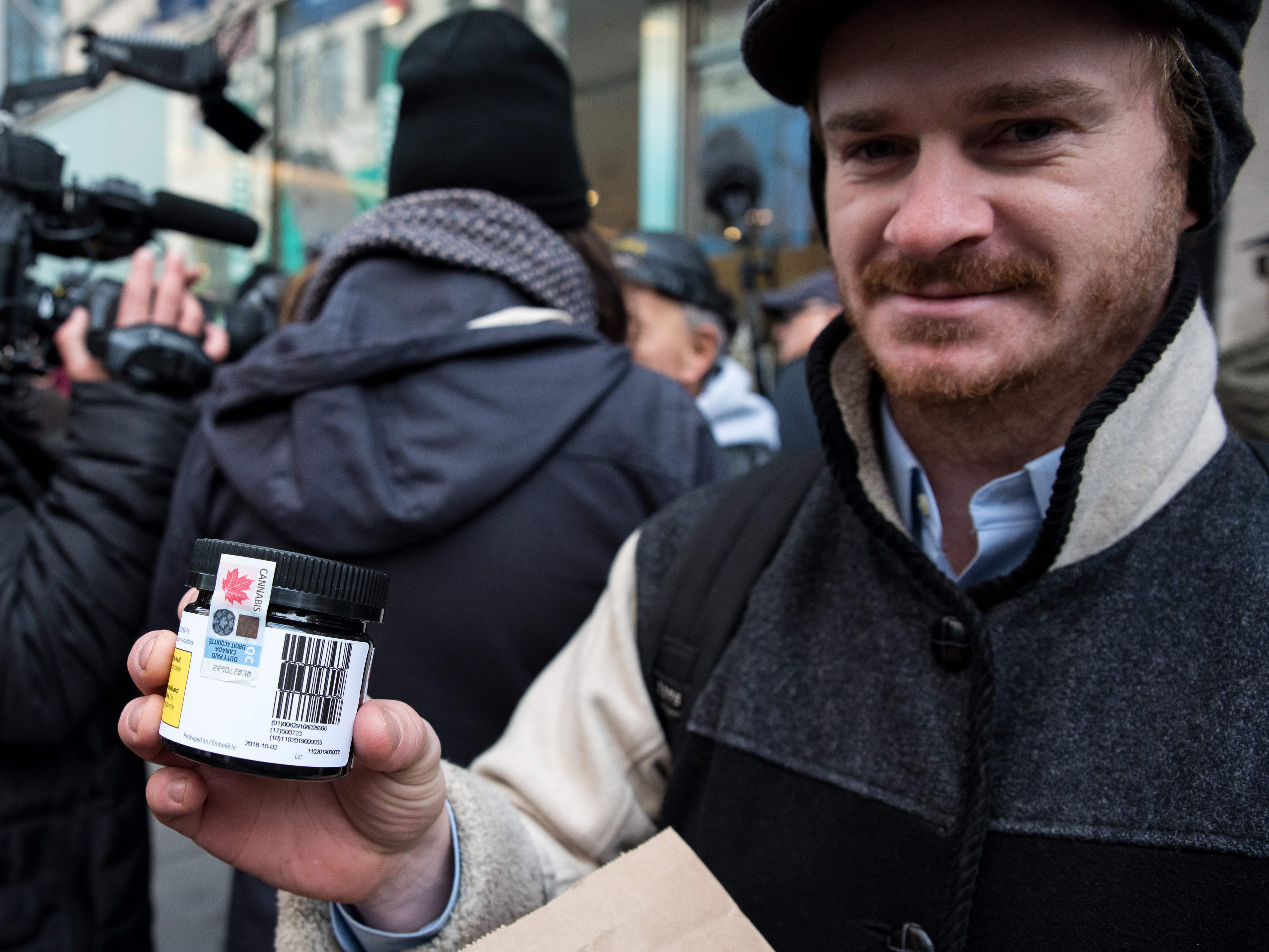 A customer shows a marijuana product that he bought after entering a cannabis store on October 17, 2018 in Montreal, Quebec. - Nearly a century of marijuana prohibition came to an end Wednesday as Canada became the first major Western nation to legalize and regulate its sale and recreational use. Scores of customers braved the cold for hours outside Tweed, a pot boutique in St John's, Newfoundland that opened briefly at midnight, to buy their first grams of legal cannabis.In total, Statistics Canada says 5.4 million Canadians will buy cannabis from legal dispensaries in 2018 -- about 15 percent of the population. Around 4.9 million already smoke. (Photo by MARTIN OUELLET-DIOTTE / AFP)MARTIN OUELLET-DIOTTE/AFP/Getty Images ORIG FILE ID: AFP_1A36J8