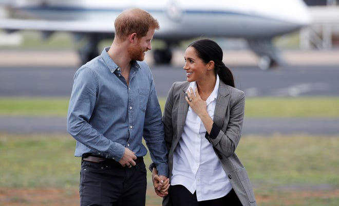 Prince Harry, Duke of Sussex, and Meghan, Duchess of Sussex, hold hands and gaze into each other's eyes as they arrive at Dubbo Airport.