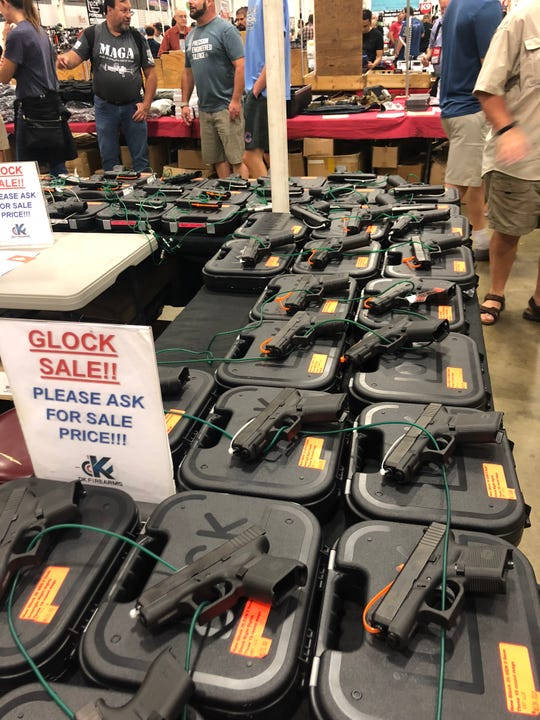 Guns are displayed at a gun show.