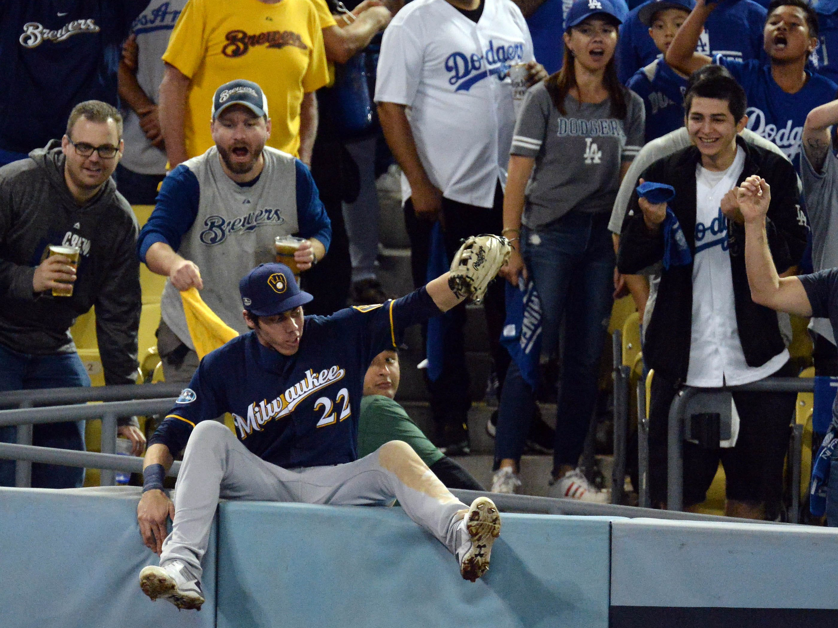 NLCS Game 4: Brewers right fielder Christian Yelich tumbles over the wall after making a catch in the seventh inning.
