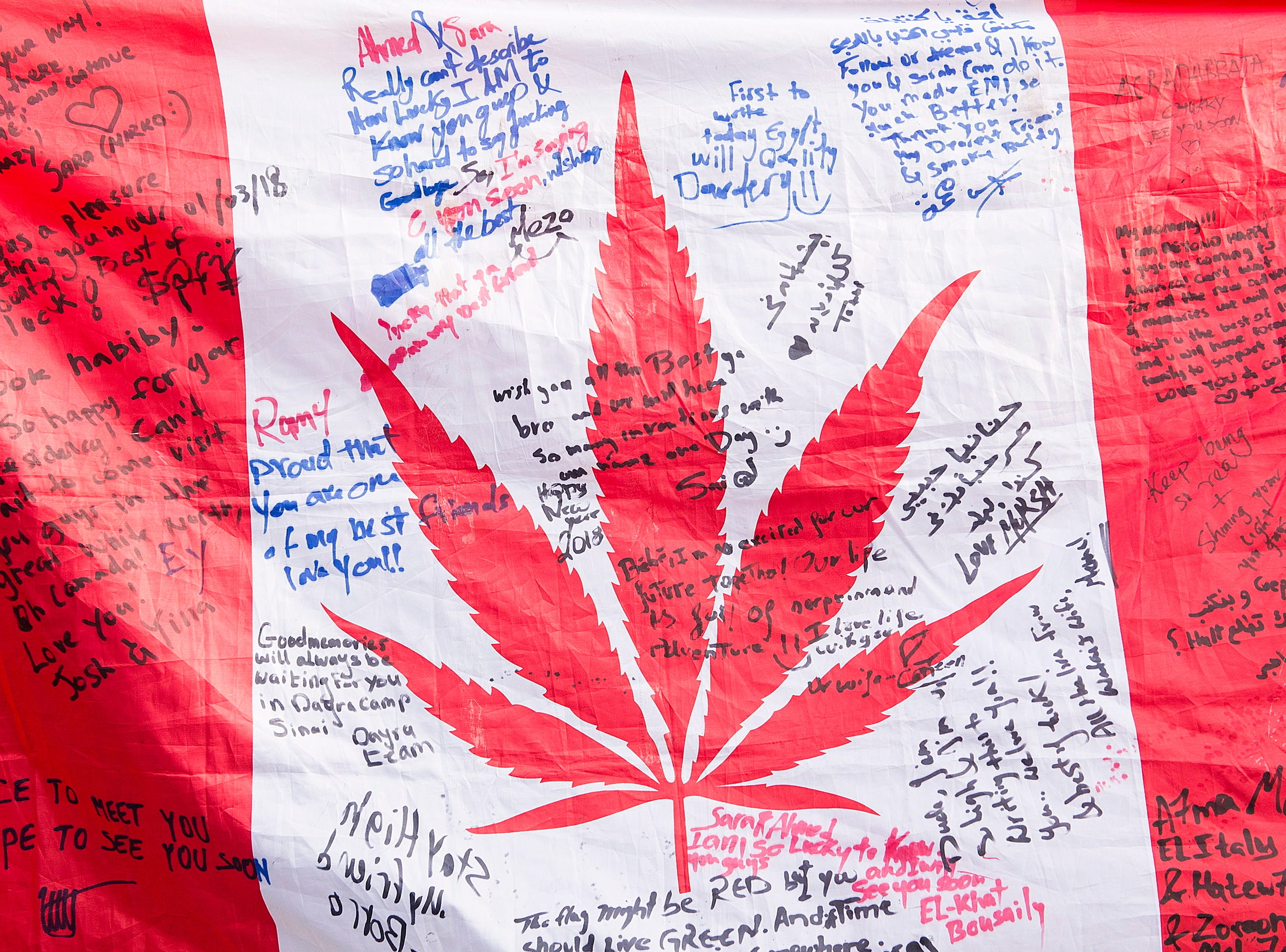 People hold up a Canadian flag with a marijuana logo on it outside a government cannabis store in Montreal, Wednesday, Oct. 17, 2018.