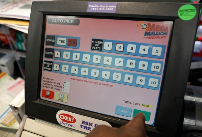 An employee presses the send button for the Mega Millions drawing, Wednesday, Oct. 17, 2018, in Lyndhurst, Ohio. The estimated jackpot for Friday's drawing would be the second-largest lottery prize in U.S. history with a jackpot estimated to exceed $900 million. (AP Photo/Tony Dejak)