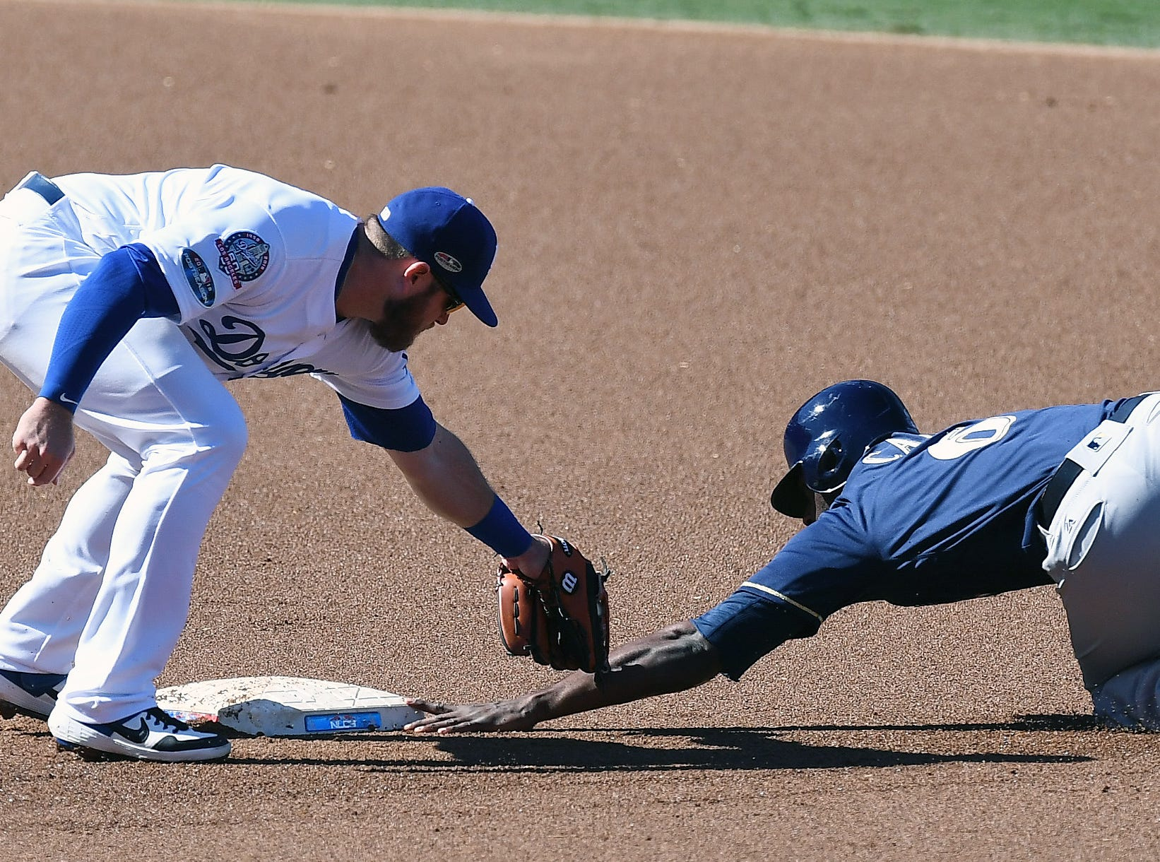 NLCS Game 5: Lorenzo Cain is caught stealing by Dodgers second baseman Max Muncy in the first inning.