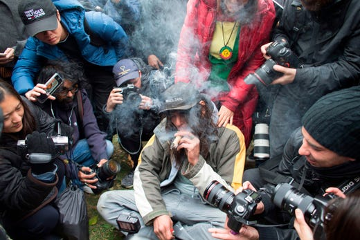 A man smokes a marijuana cigarette during a legalization party at Trinity Bellwoods Park in Toronto, Ontario, Oct. 17, 2018.  Nearly a century of marijuana prohibition came to an end Wednesday as Canada became the first major Western nation to legalize and regulate its sale and recreational use. Scores of customers braved the cold for hours outside Tweed, a pot boutique in St John's, Newfoundland that opened briefly at midnight, to buy their first grams of legal cannabis.In total, Statistics Canada says 5.4 million Canadians will buy cannabis from legal dispensaries in 2018, about 15 percent of the population. Around 4.9 million already smoke.