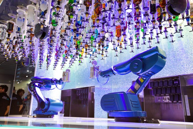 Two robotic arms mix drinks at the Bionic Bar on Royal Caribbean's Quantum of the Seas.