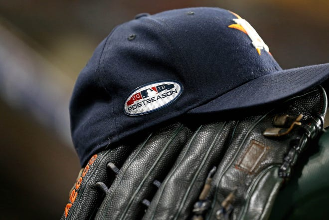 The cap and glove of Houston Astros right fielder Josh Reddick on the dugout railing.