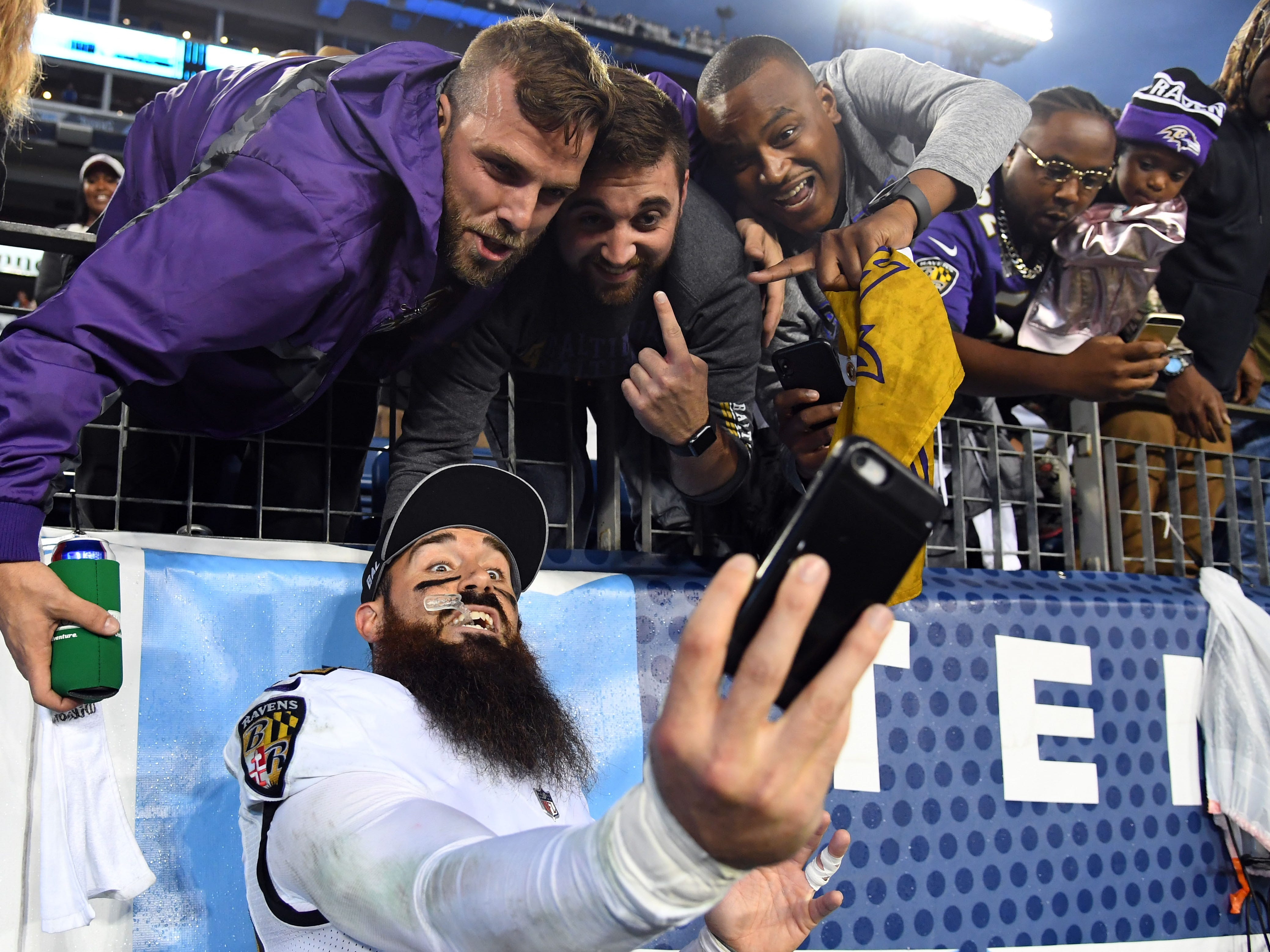 Baltimore Ravens free safety Eric Weddle poses for a selfie with fans after a win against the Tennessee Titans at Nissan Stadium.
