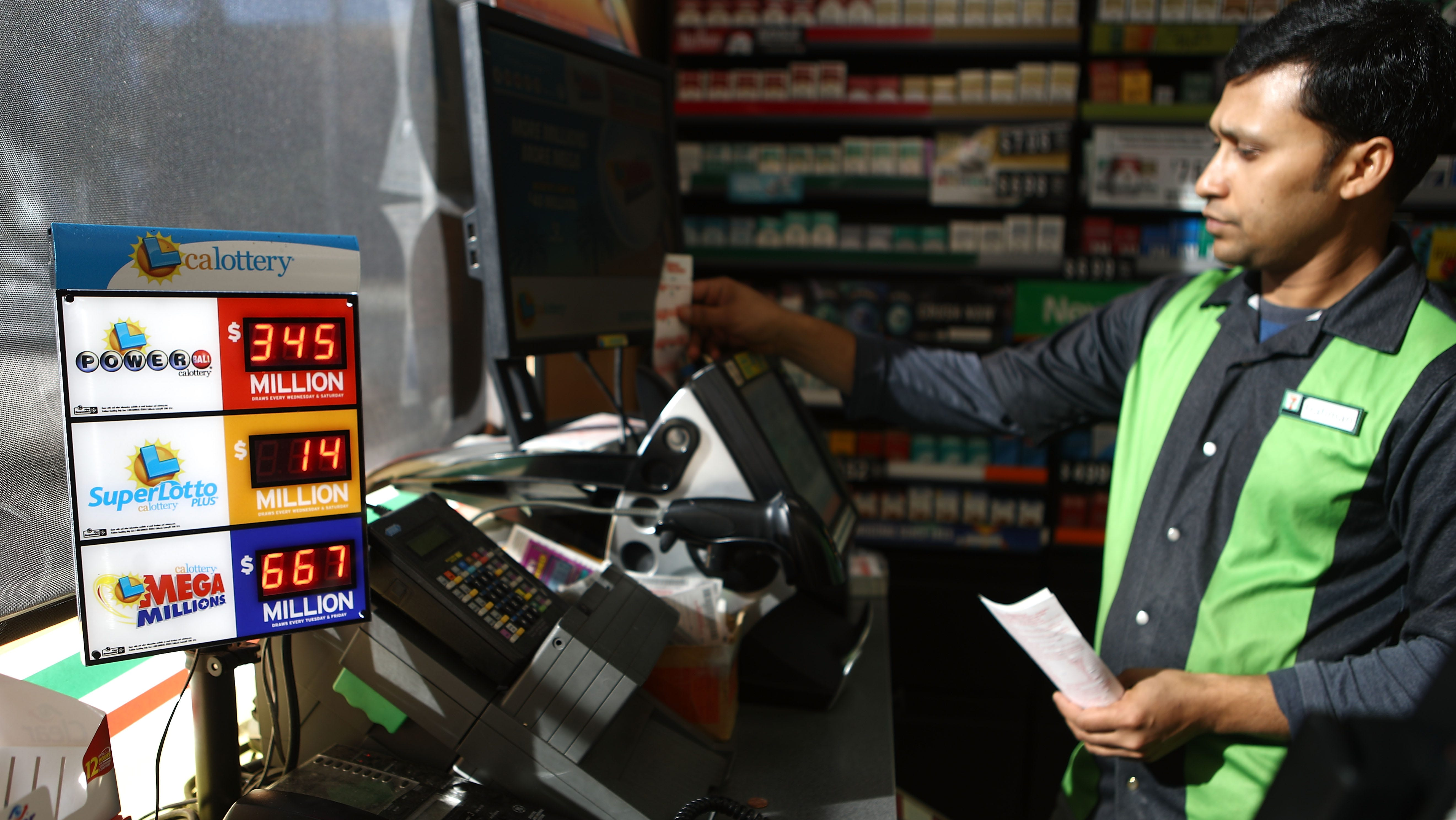 A worker processes lottery tickets on October 16, 2018 in Los Angeles, California. Friday's Mega Millions jackpot jumps to $868 million while Wednesday night's Powerball jackpot is at $345 million.