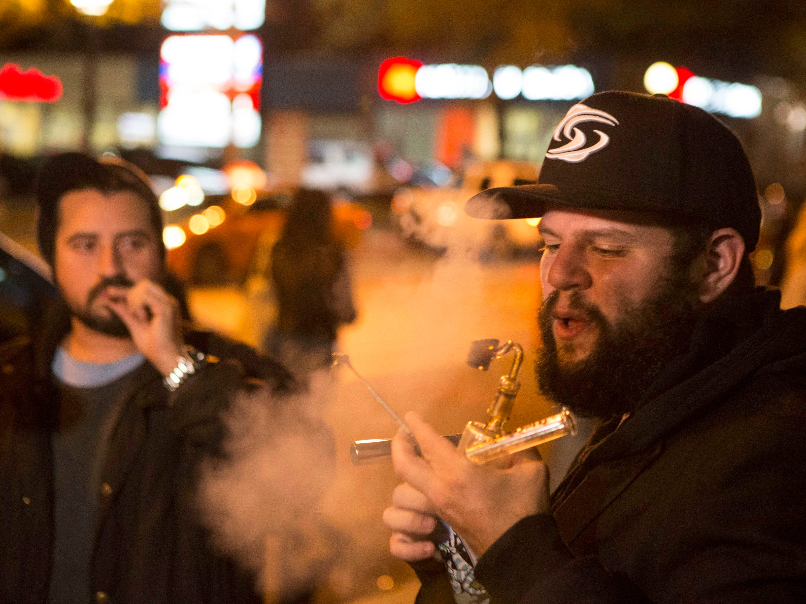 People smoke cannabis on the street in Toronto on Wednesday, Oct. 17, 2018. Canada became the largest country with a legal national marijuana marketplace as sales began early Wednesday in Newfoundland. (Chris Young/The Canadian Press via AP) ORG XMIT: CHY109