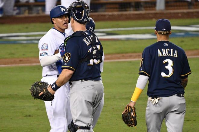 Brewers catcher Erik Kratz, right, confronts Dodgers shortstop Manny Machcado after Machado kicked the leg of first baseman Jesus Aguilar.