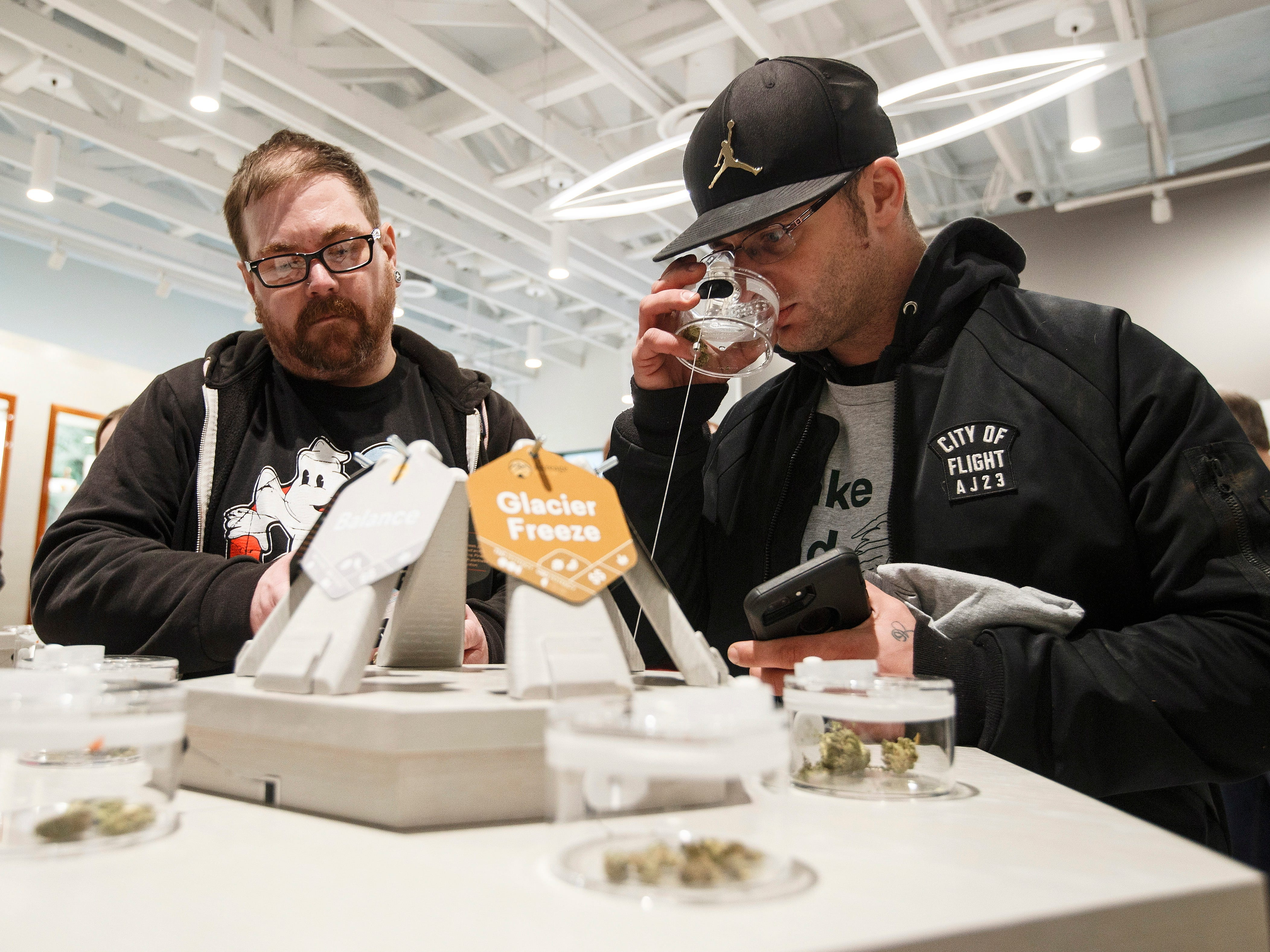 Customers smell samples of cannabis at the opening of Fire and Flower in Edmonton, Alberta, on Wednesday, Oct. 17, 2018. Canada became the largest country with a legal national marijuana marketplace as sales began early Wednesday. (Jason Franson/The Canadian Press via AP) ORG XMIT: EDM103