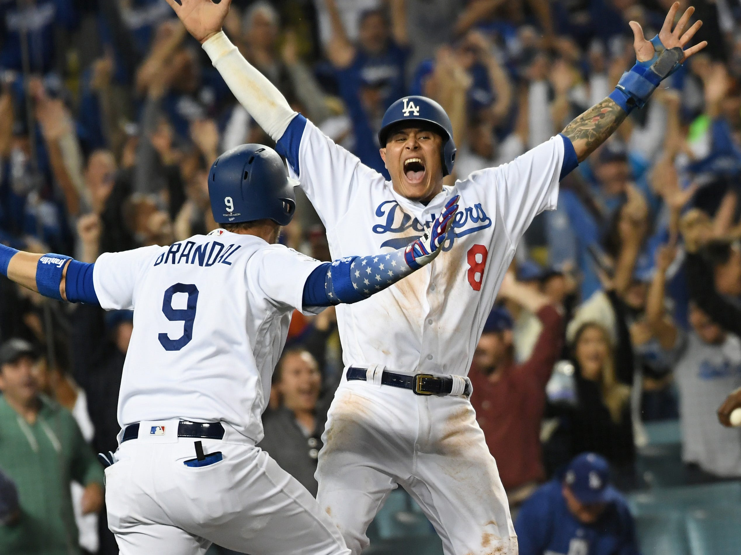 NLCS Game 4: Dodgers shortstop Manny Machado scores the winning run and is met by catcher Yasmani Grandal in the 13th inning.