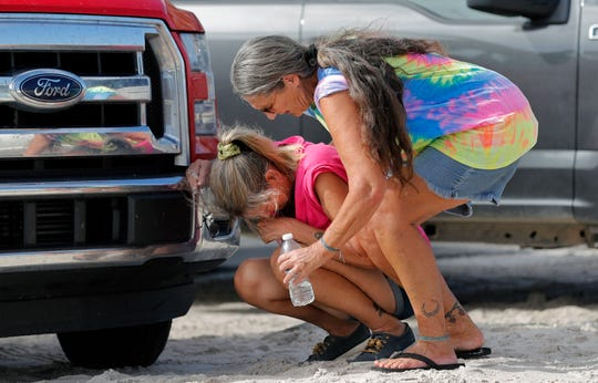 Nancy Register weeps as she is comforted by Roxie Cline, right, after she lost her home and all the contents inside to Hurricane Michael in Mexico Beach, Fla.