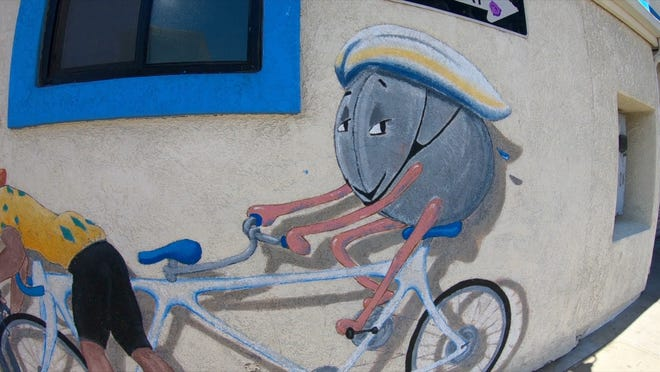 A mural on the side of the Splash Cafe shows a clam taking a bike ride.