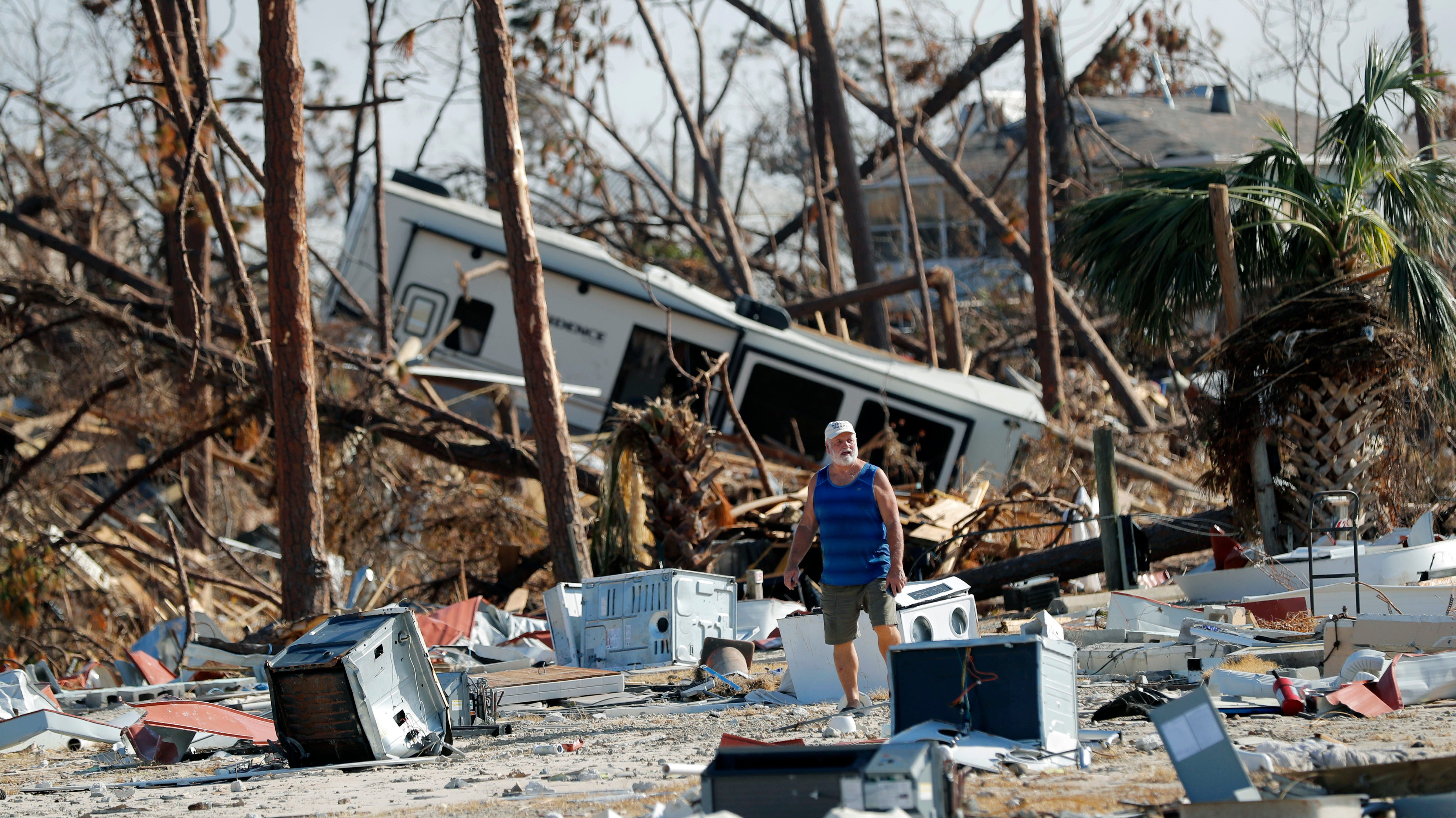 Ronnie Poole walks through debris as he checks on a friend's home in the aftermath of Hurricane Michael in Mexico Beach, Fla., Wednesday, Oct. 17, 2018.