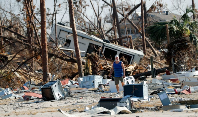 Ronnie Poole walks through debris as he checks on a friend's home in the aftermath of Hurricane Michael in Mexico Beach, Fla., on Oct. 17, 2018.