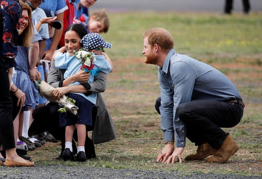 A young fan hugs the Duchess Meghan, and also Prince Harry, as the royals arrive in Dubbo.
