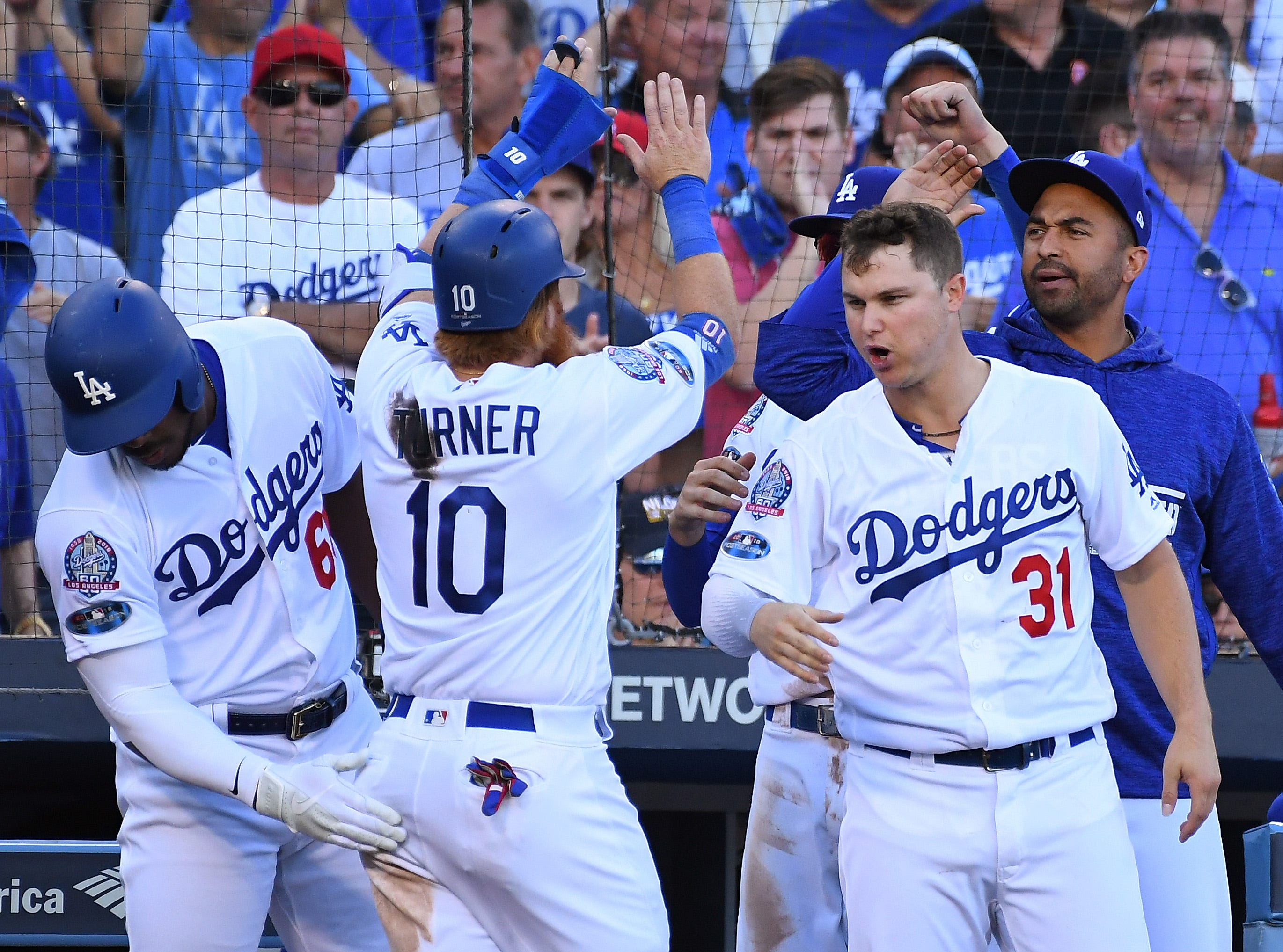 NLCS Game 5: Justin Turner celebrates with teammates after scoring a run in the sixth inning.
