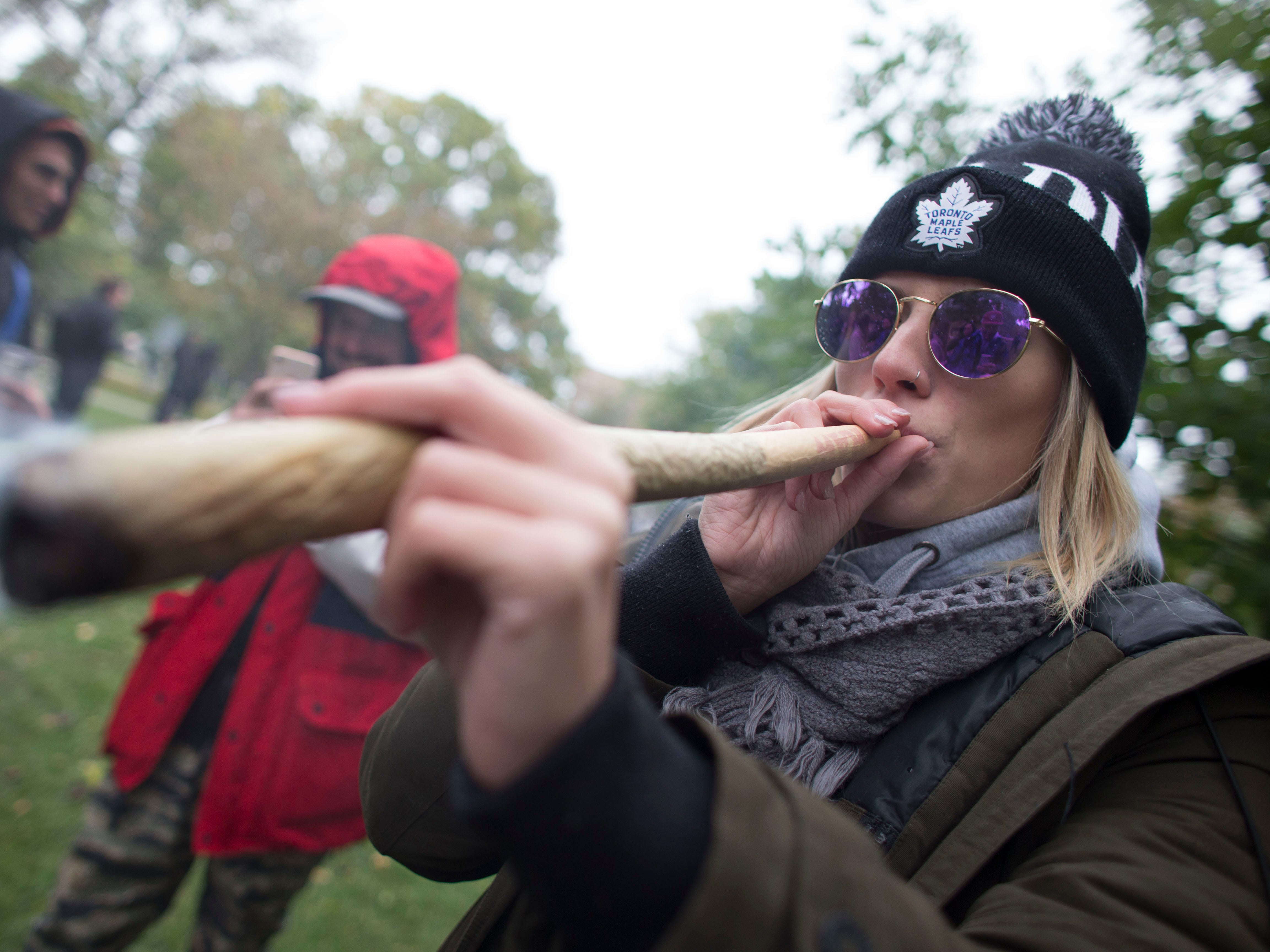 A woman smokes a marijuana cigarette during a legalization party at Trinity Bellwoods Park in Toronto, Ontario, Oct. 17, 2018.