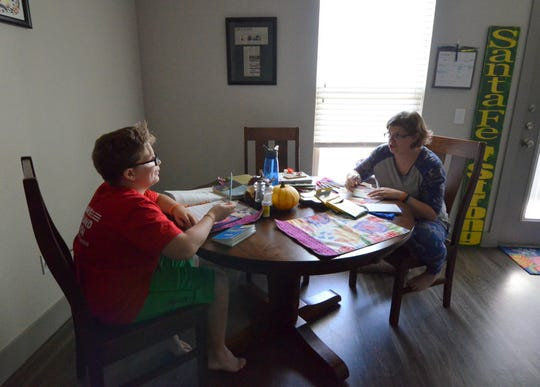Rhonda Hart, whose daughter Kimberly Vaughan was killed in the Santa Fe High School Shooting, works at her kitchen table with her son, Tyler.