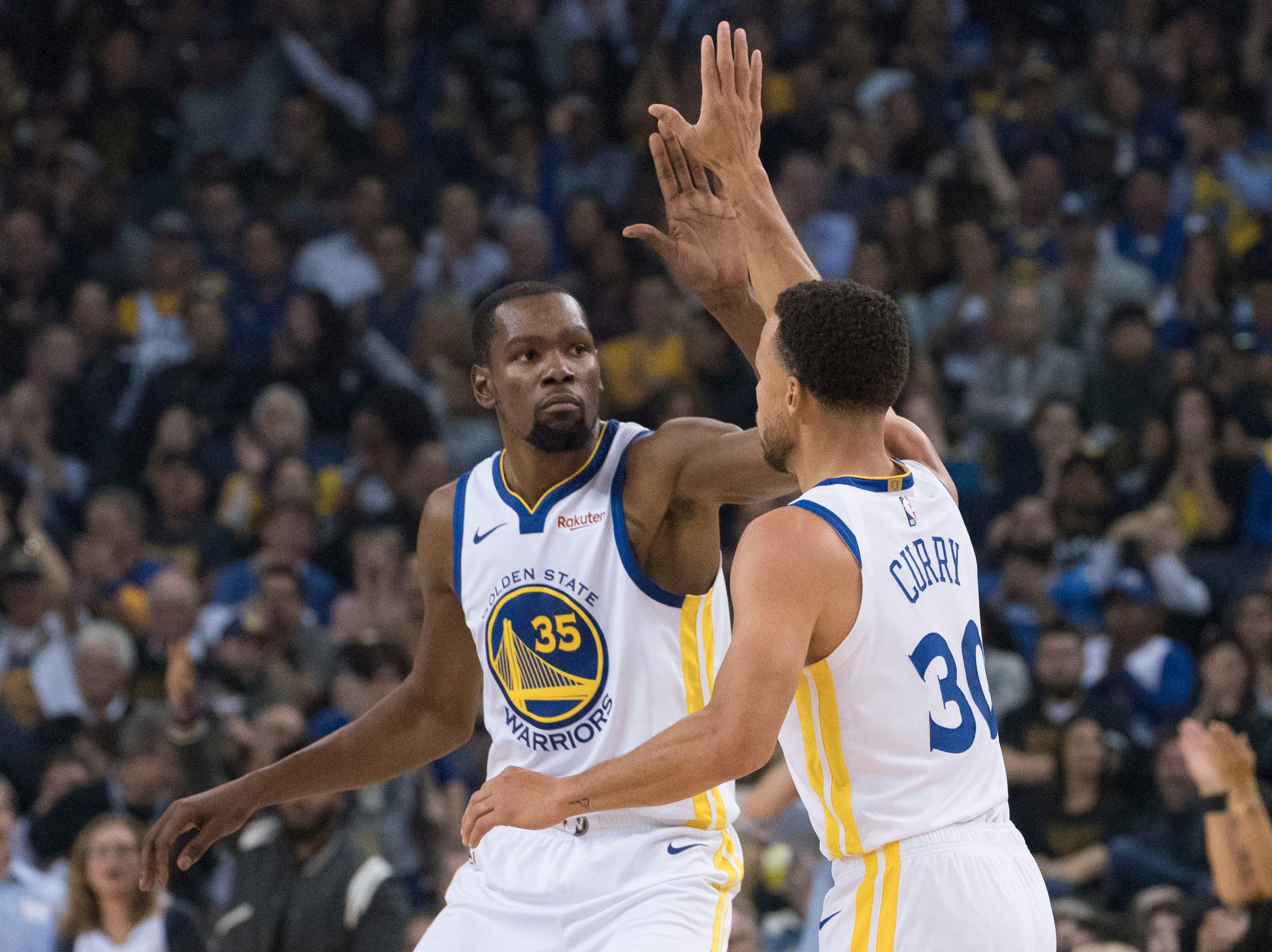 Oct. 16: Golden State Warriors forward Kevin Durant (35) congratulates guard Stephen Curry (30) for making a three-point basket against the Oklahoma City Thunder.