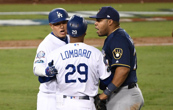 Dodgers first base coach George Lombard  looks to break up a possible confrontation after Manny Machado ran into the leg of Brewers first baseman Jesus Aguilar in the 10th inning of NLCS Game 4.