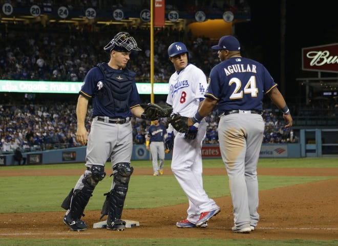 Manny Machado and Jesus Aguilar exchange words after Machado's foot hit Aguilar's on his way to being thrown out at first base in the 10th inning.