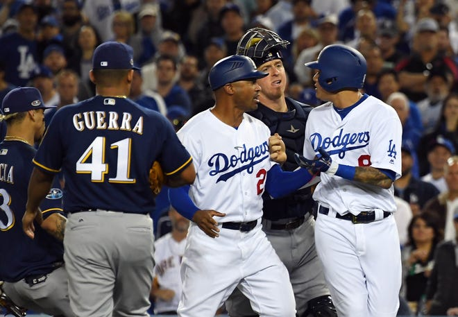 Dodgers shortstop Manny Machado and Jesus Aguilar exchange words at first base in the 10th inning.