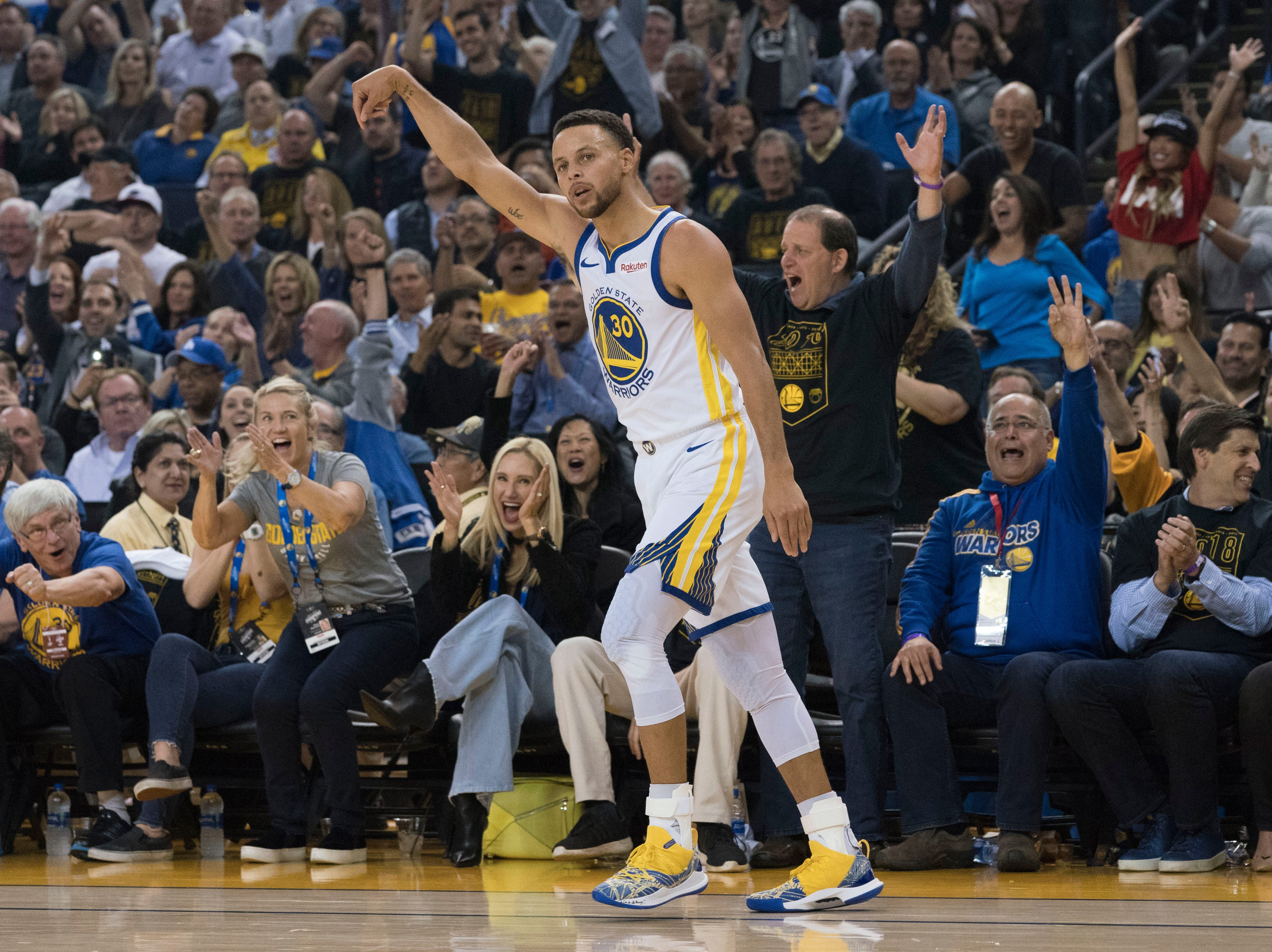 Oct. 16: Golden State Warriors guard Stephen Curry celebrates after making a three-point basket against the Oklahoma City Thunder.